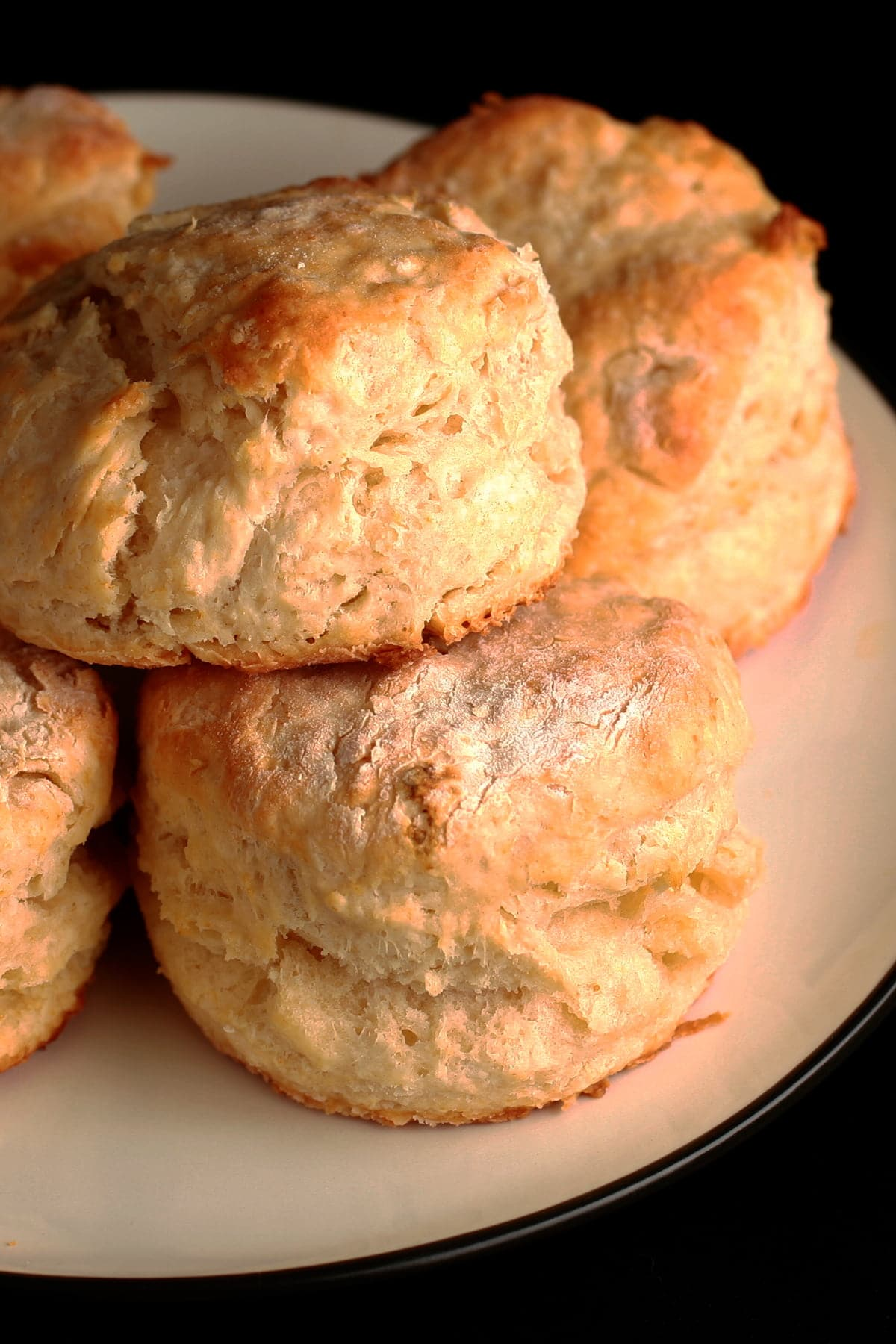 A small plate, stacked with golden baking powder biscuits.