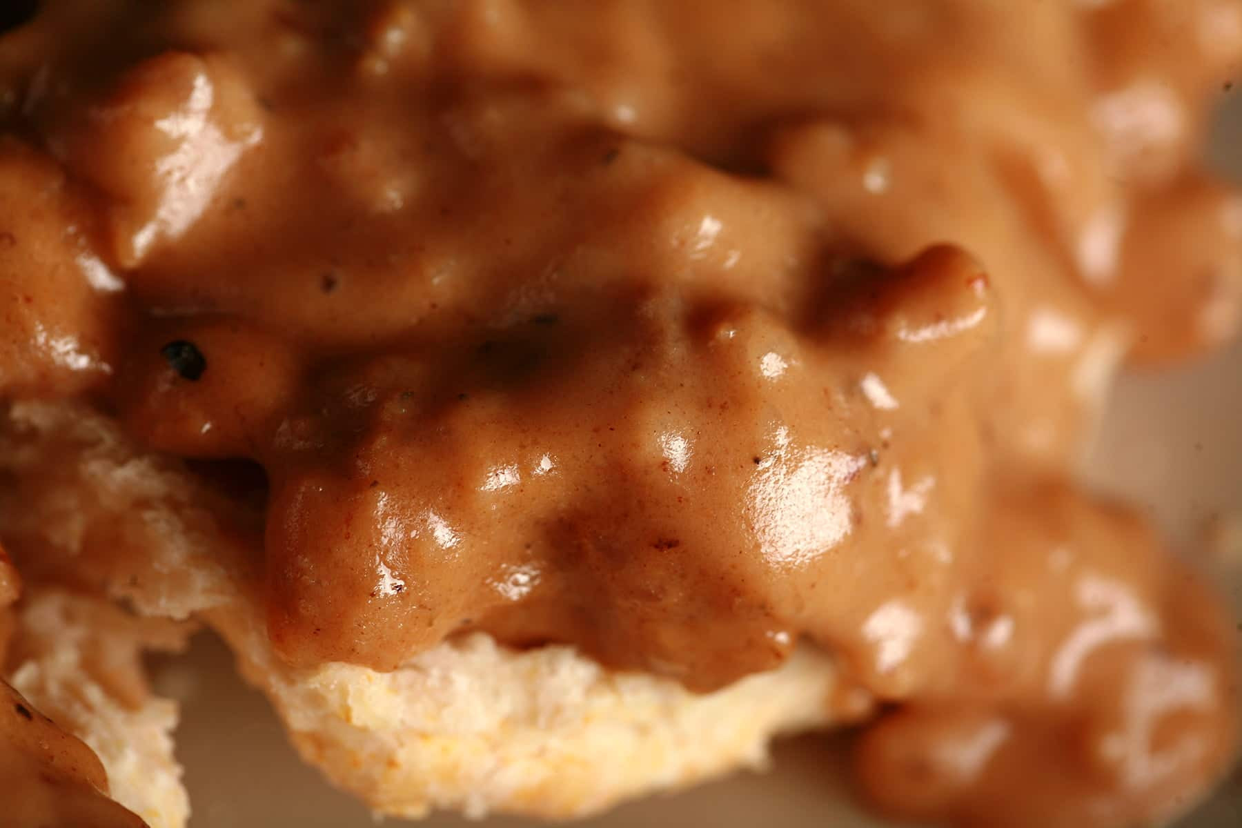 A close up view of a split biscuit covered with sausage gravy - Biscuits and Gravy, My Way!