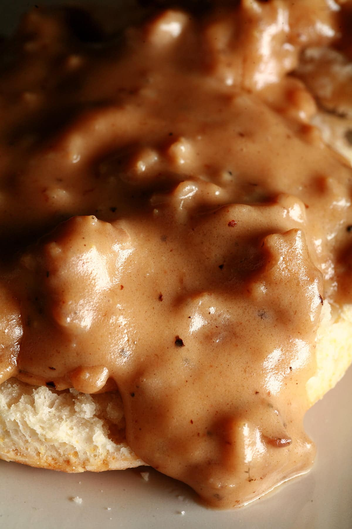 A close up view of a split biscuit covered with sausage gravy.