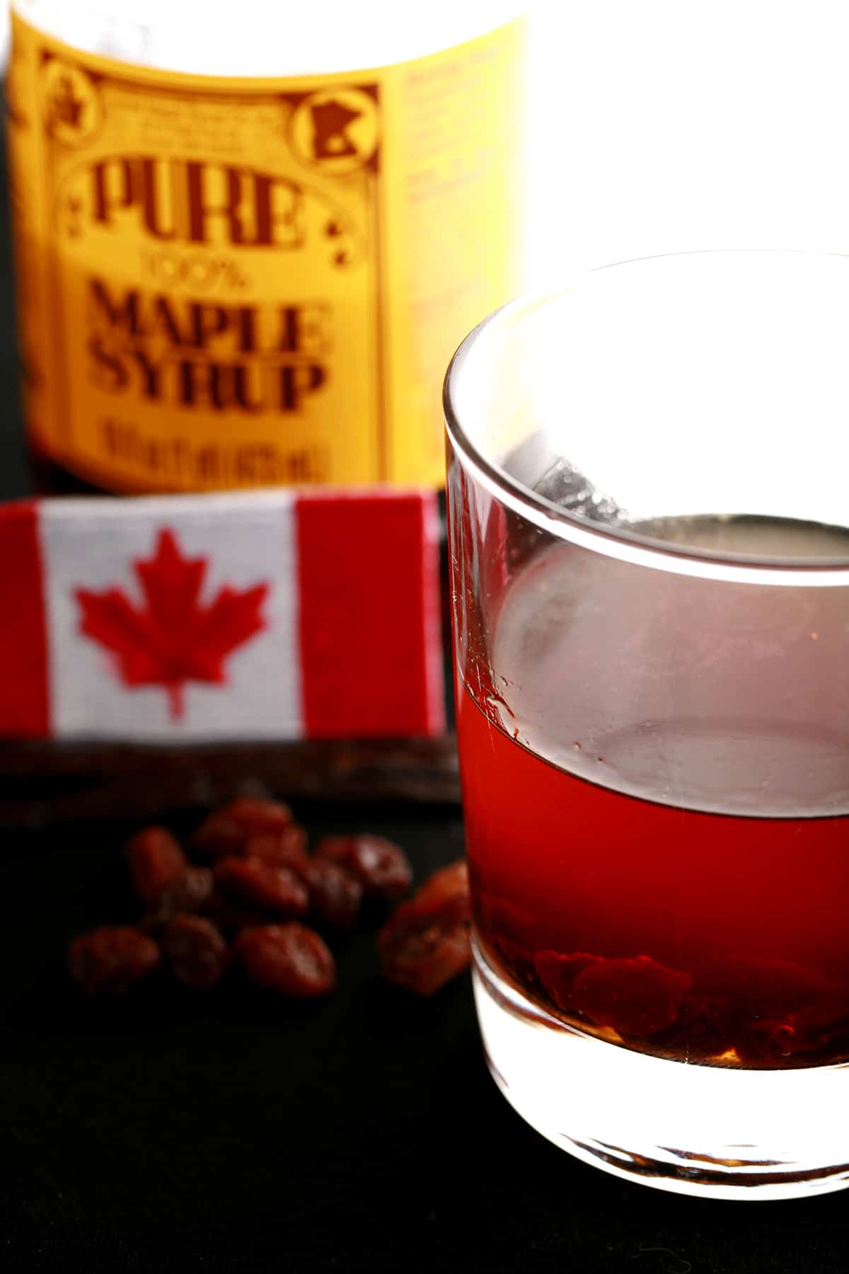A tumbler glass of maple butter tart liqueur, next to a bottle of maple syrip and a small Canadian flag.