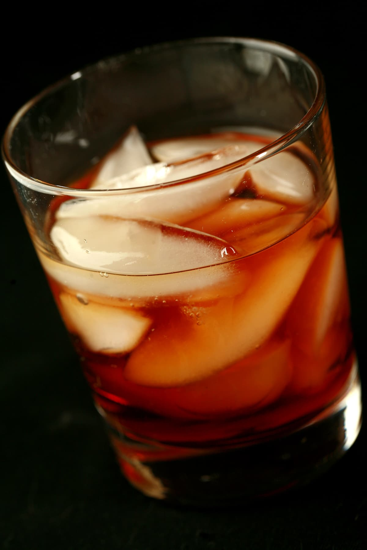A tumbler glass with ice and a rich maple coloured liqueur.