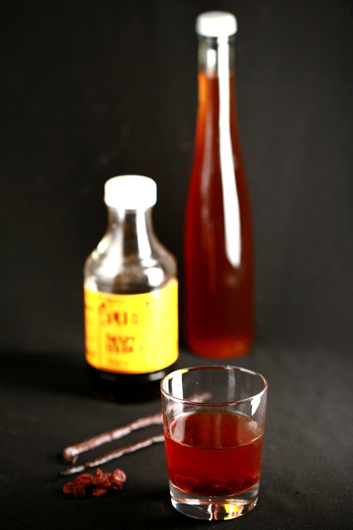A glass of maple butter tart liqueur next to a bottle of the liqueur, and a bottle of maple syrup.