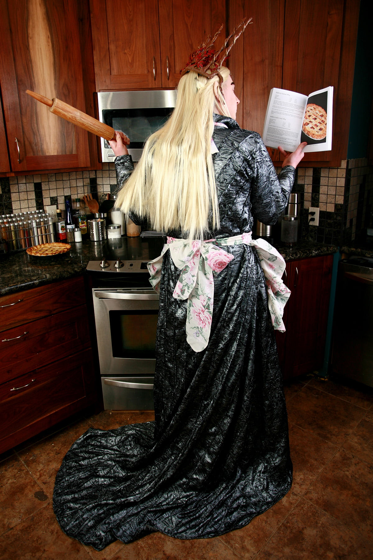 A man dressed as Thrandruil, with his back to the camera.  He is wearing a frilly apron over his robe, and is reading a cookbook.  In one hand, he holds a rolling pin.