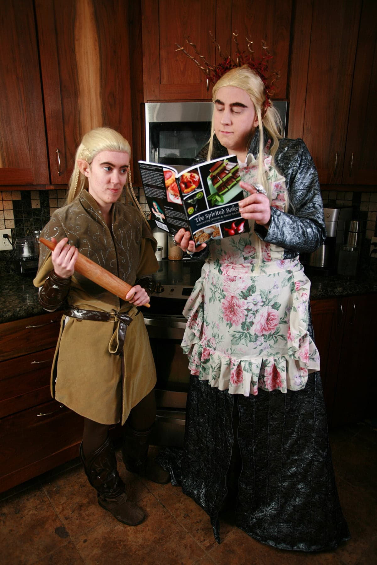 Cosplayers dressed as Thranduil and Legolas are in the kitchen, reading a cookbook.