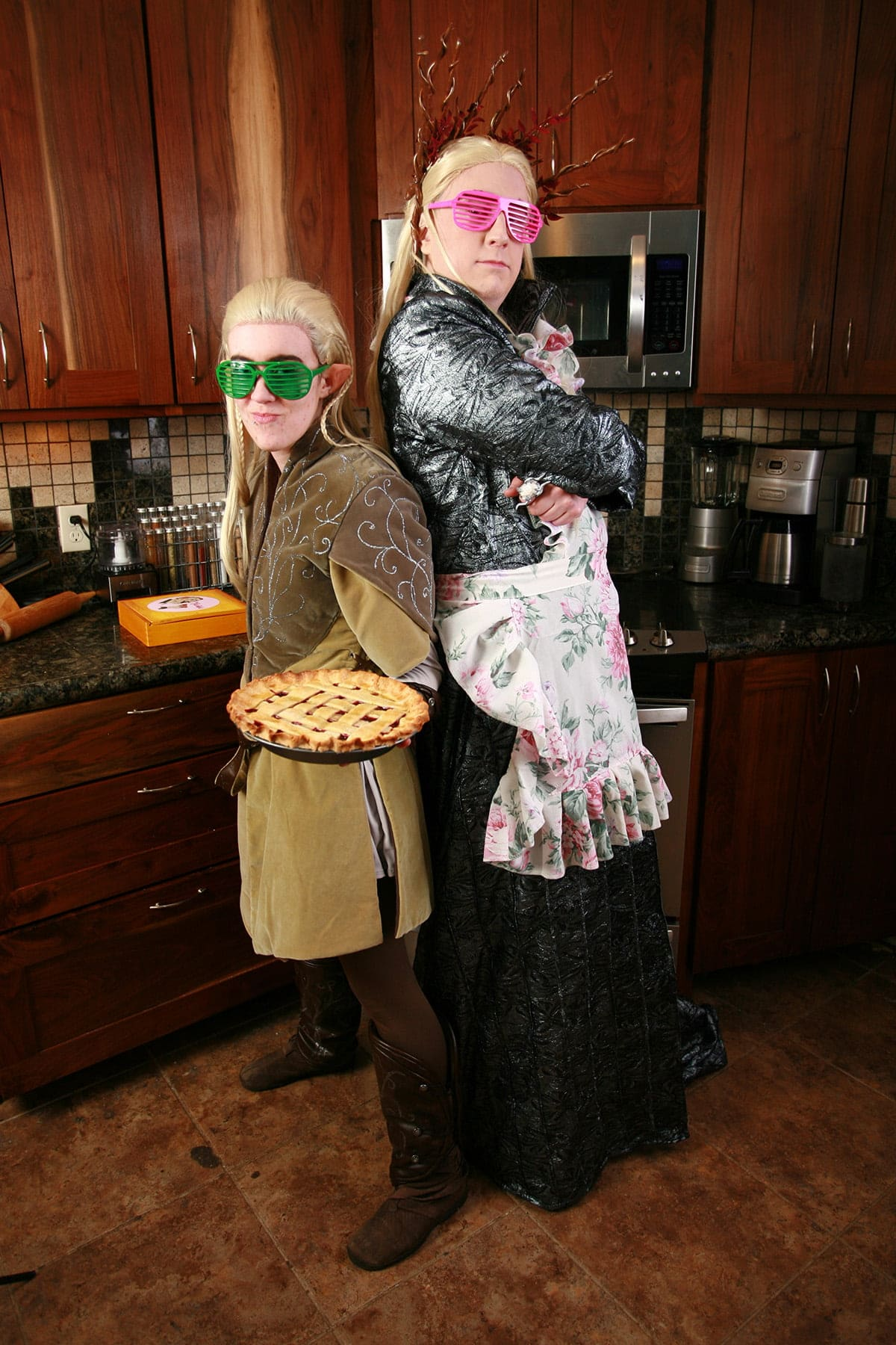 Cosplayers dressed as Thranduil and Legolas are back to back in the kitchen. Legolas is holding a pie, and both are wearing 80s style slat sunglasses.