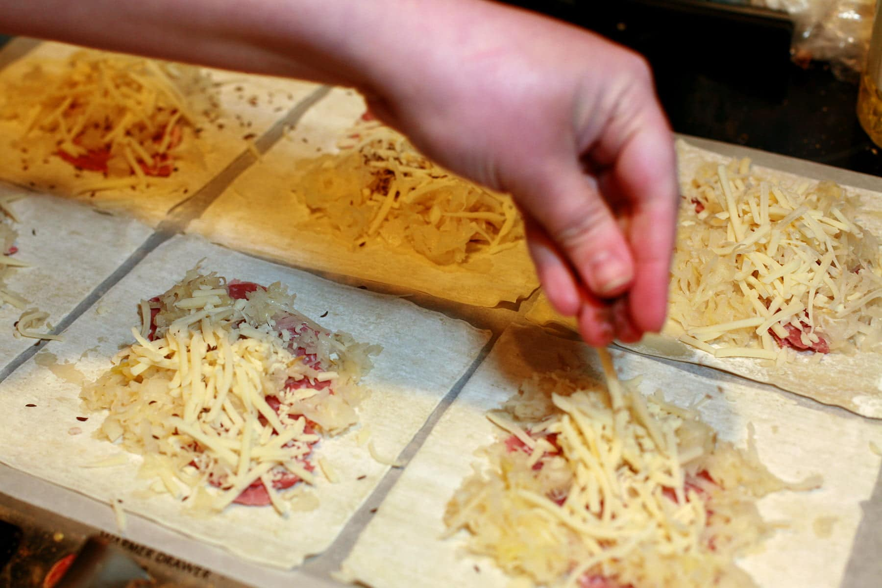 Wonton wrappers are arranged on a work surface. Each has meat, sauerkraut, and swiss cheese on top. A hand sprinkles caraway seeds over them.