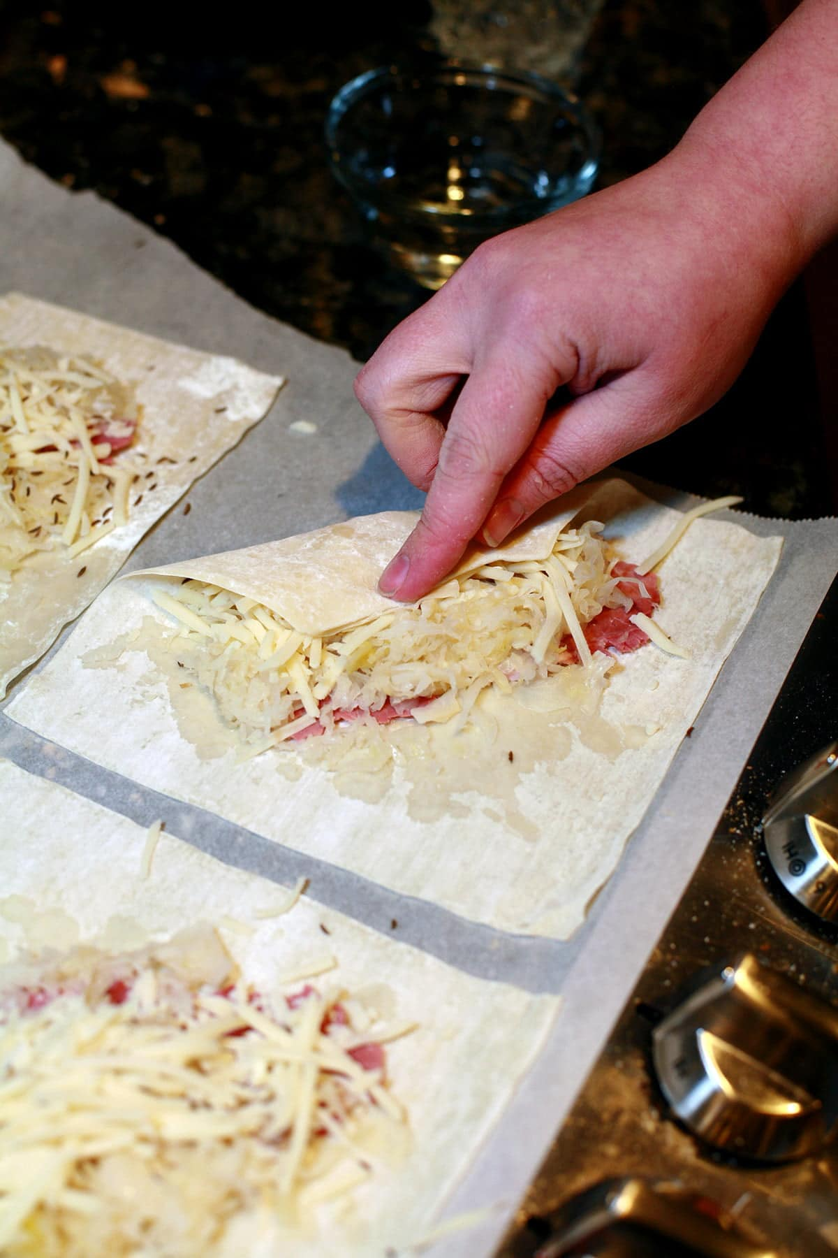 A hand is shown folding a corner of a wonton wrapper over the filling that's arranged in the middle of that wrapper.