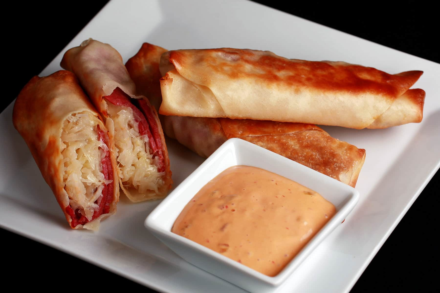 A white plate is piled with baked Reuben poppers, with one cut in half. There is a small bowl of thousand island dressing on the plate, as well.