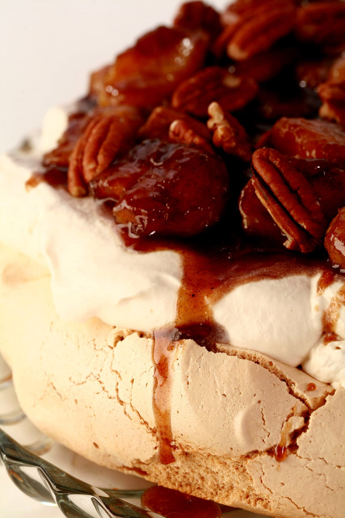 A very close up view of a brown sugar pavlova, topped with bananas foster.