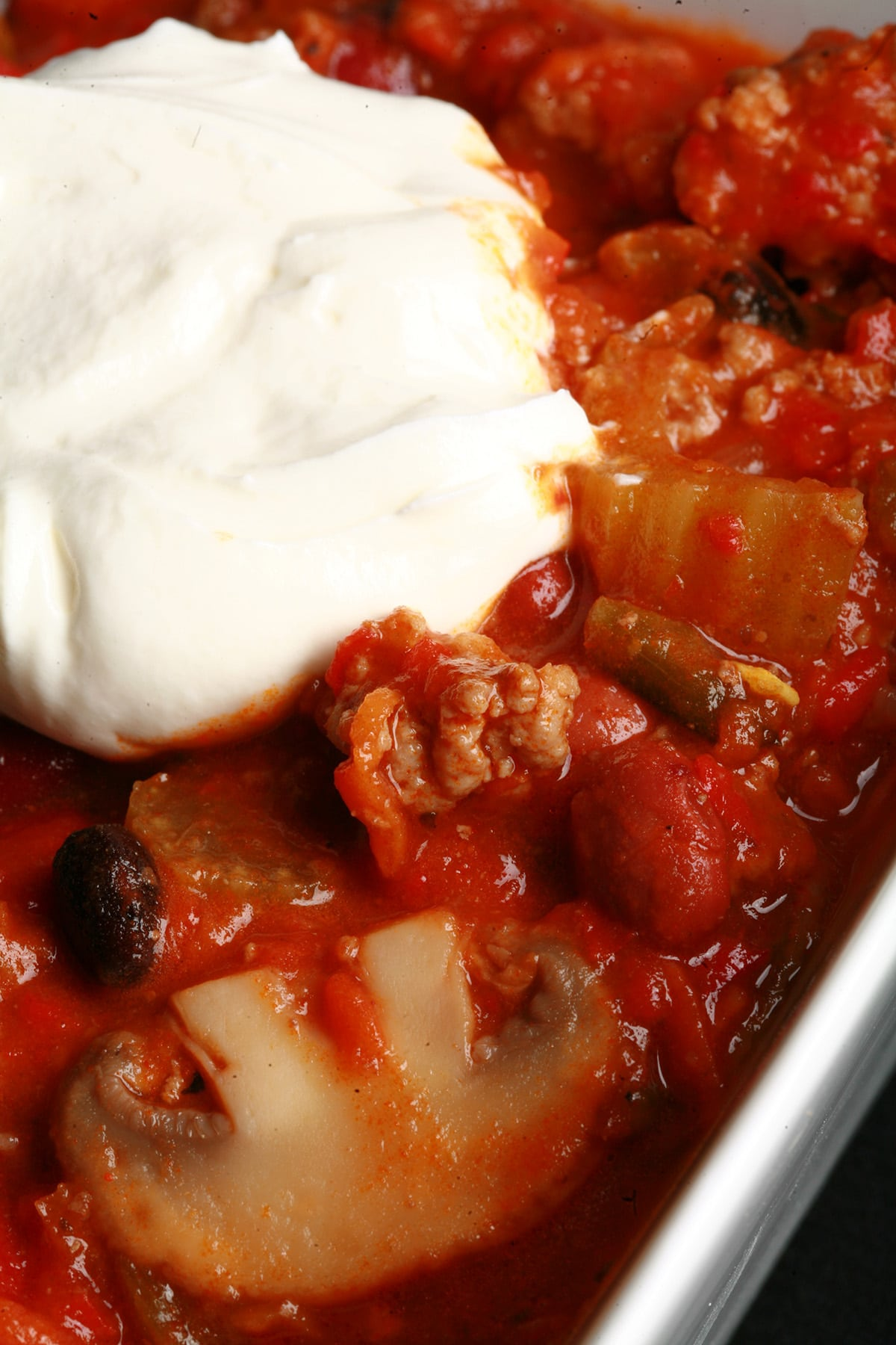 Close up photo of a bowl of roasted convention chili. Kidney beans, ground beef, mushrooms, celery, and red peppers are visible, and there is a dollop of sour cream on top.