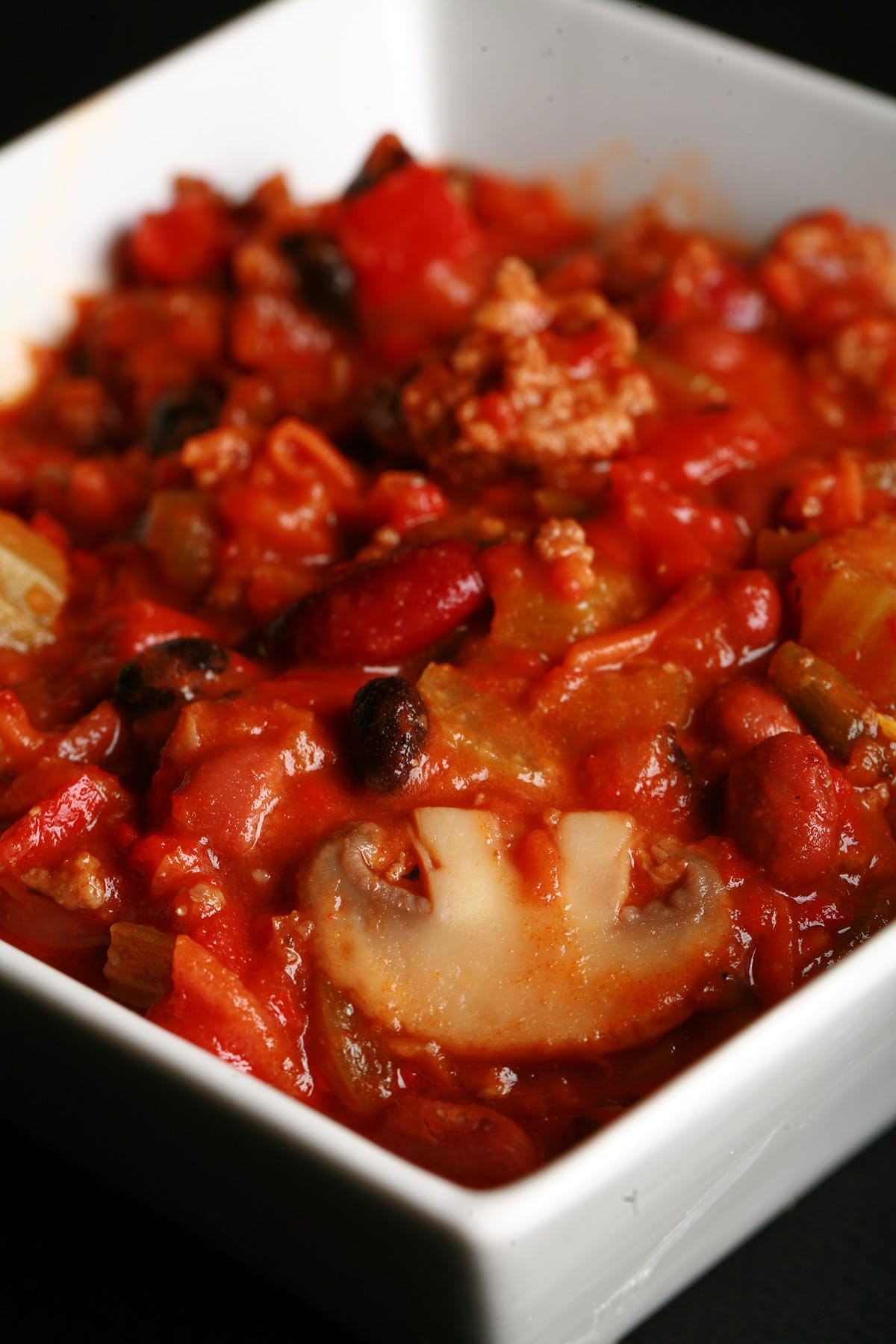 Close up photo of a bowl of chili. Kidney beans, ground beef, mushrooms, celery, and red peppers are visible.