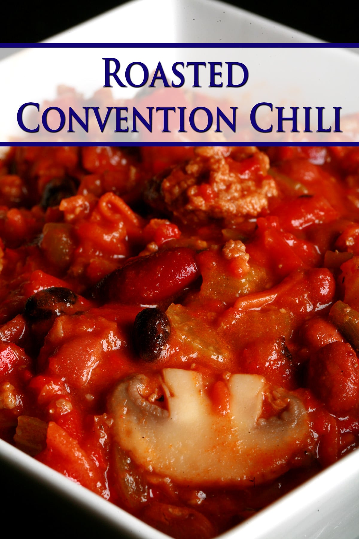 Close up photo of a bowl of roasted convention chili. Kidney beans, ground beef, mushrooms, celery, and red peppers are visible.