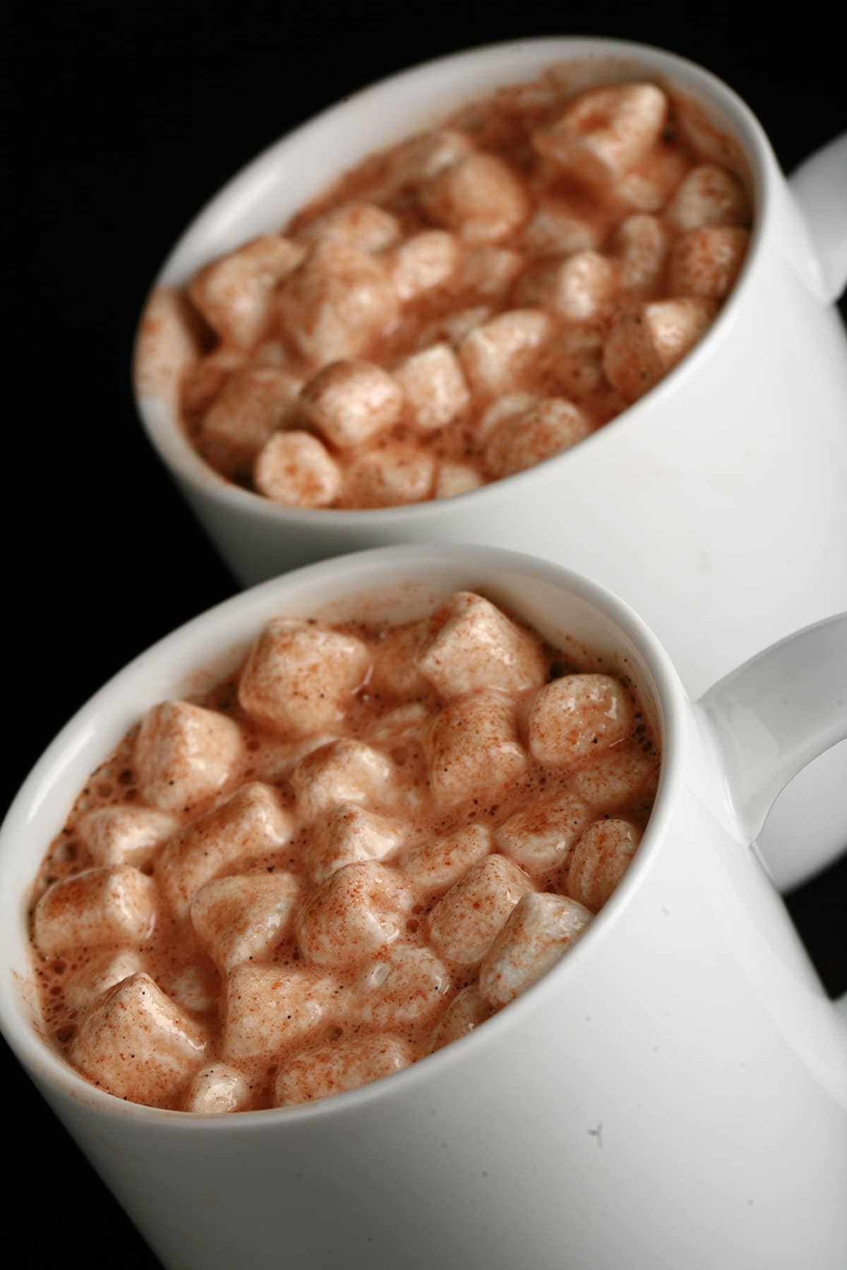 2 white mugs of grownup hot chocolate, with mini marshmallows and alcohol.