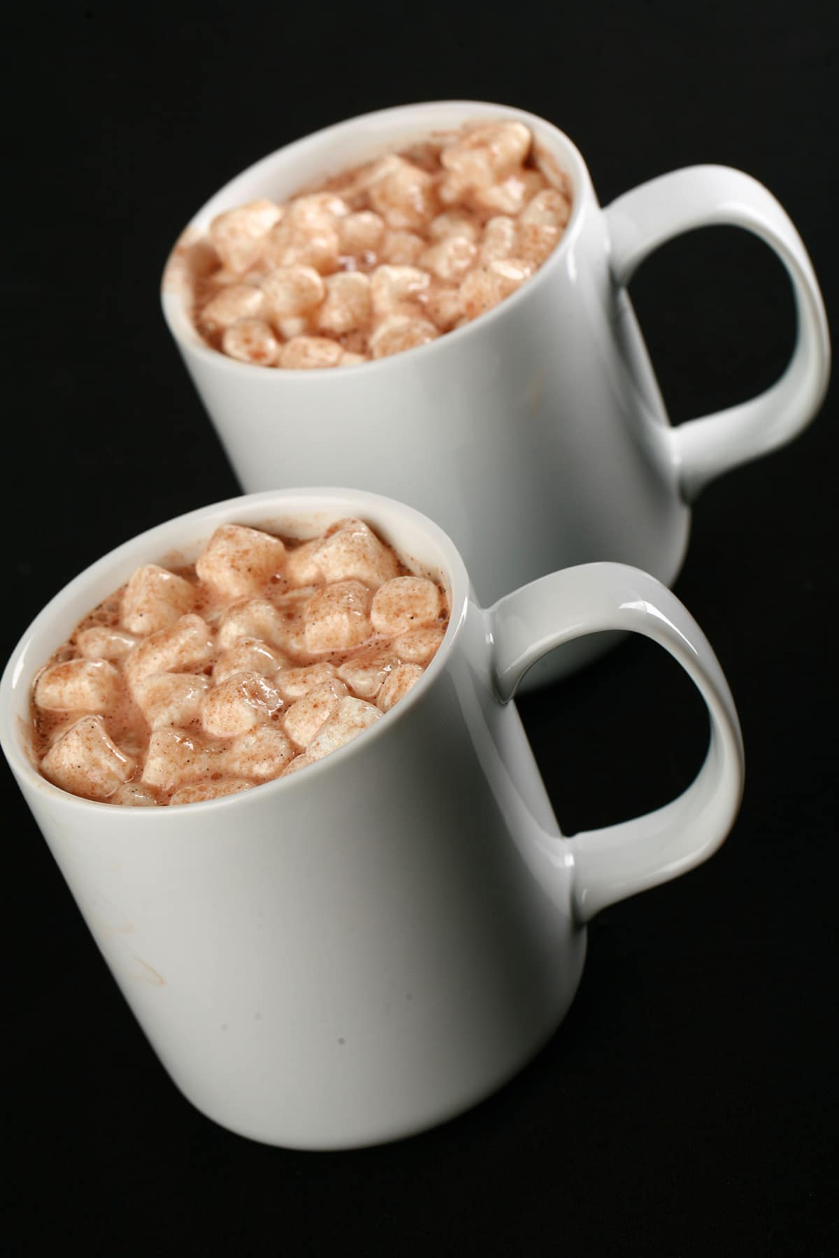 2 white mugs of grownup hot cocoa, with mini marshmallows and alcohol.