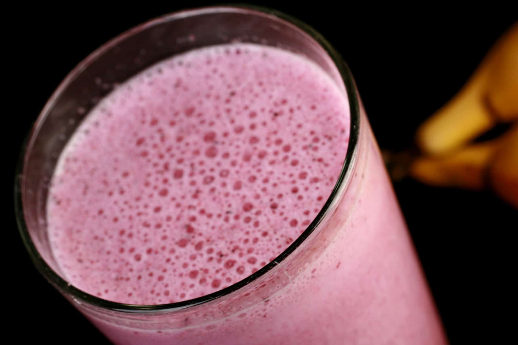 A close up view of a pink coloured smoothie in a tall glass.