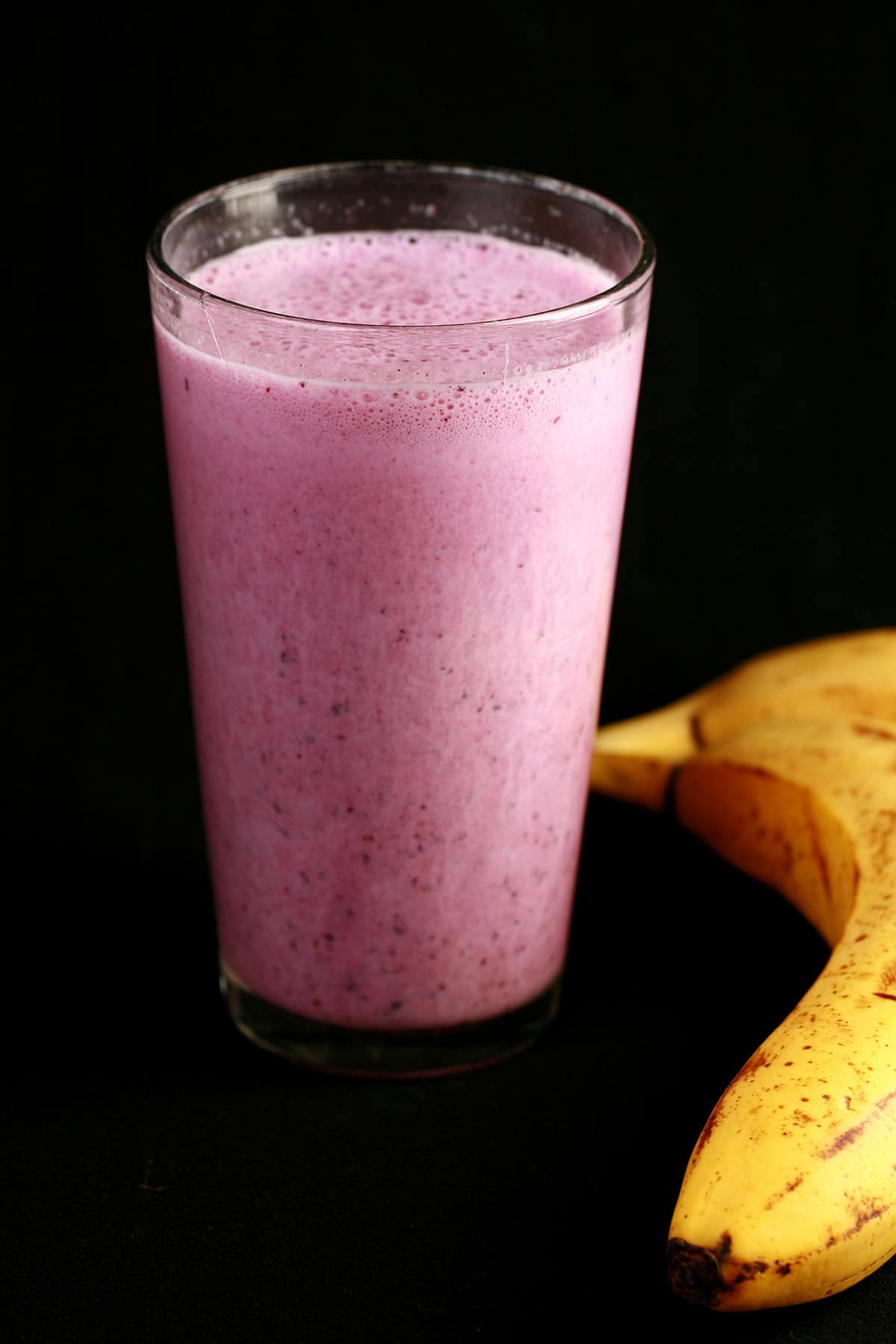 A pink hotel room smoothie in a tall glass, next to 2 bananas.