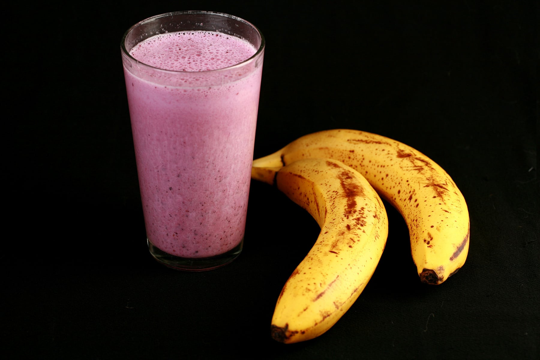 A pink convention smoothie in a tall glass, next to 2 bananas.