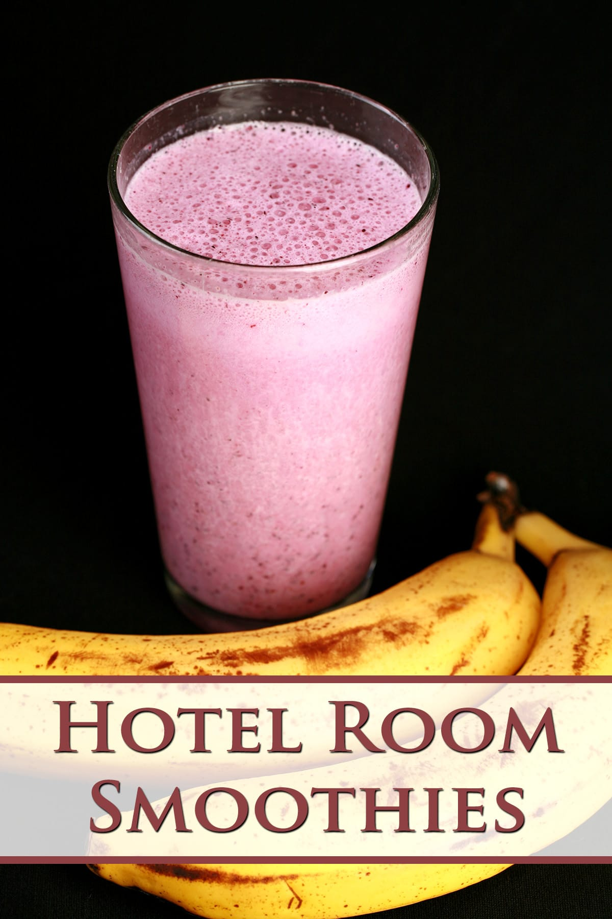 A pink convention smoothie in a tall glass, next to 2 bananas. Red text overlay says hotel room smoothies.