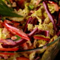 A glass bowl is filled with a colourful coleslaw. Red pepper, purple and green cabbage, carrot, and green onions are all visible.