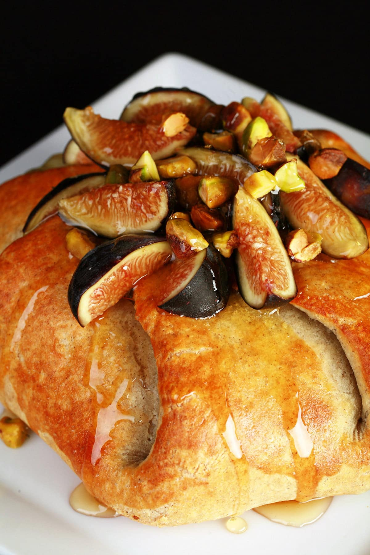 Sliced figs, pistachio, and honey top a round, gathered, golden brown pastry.