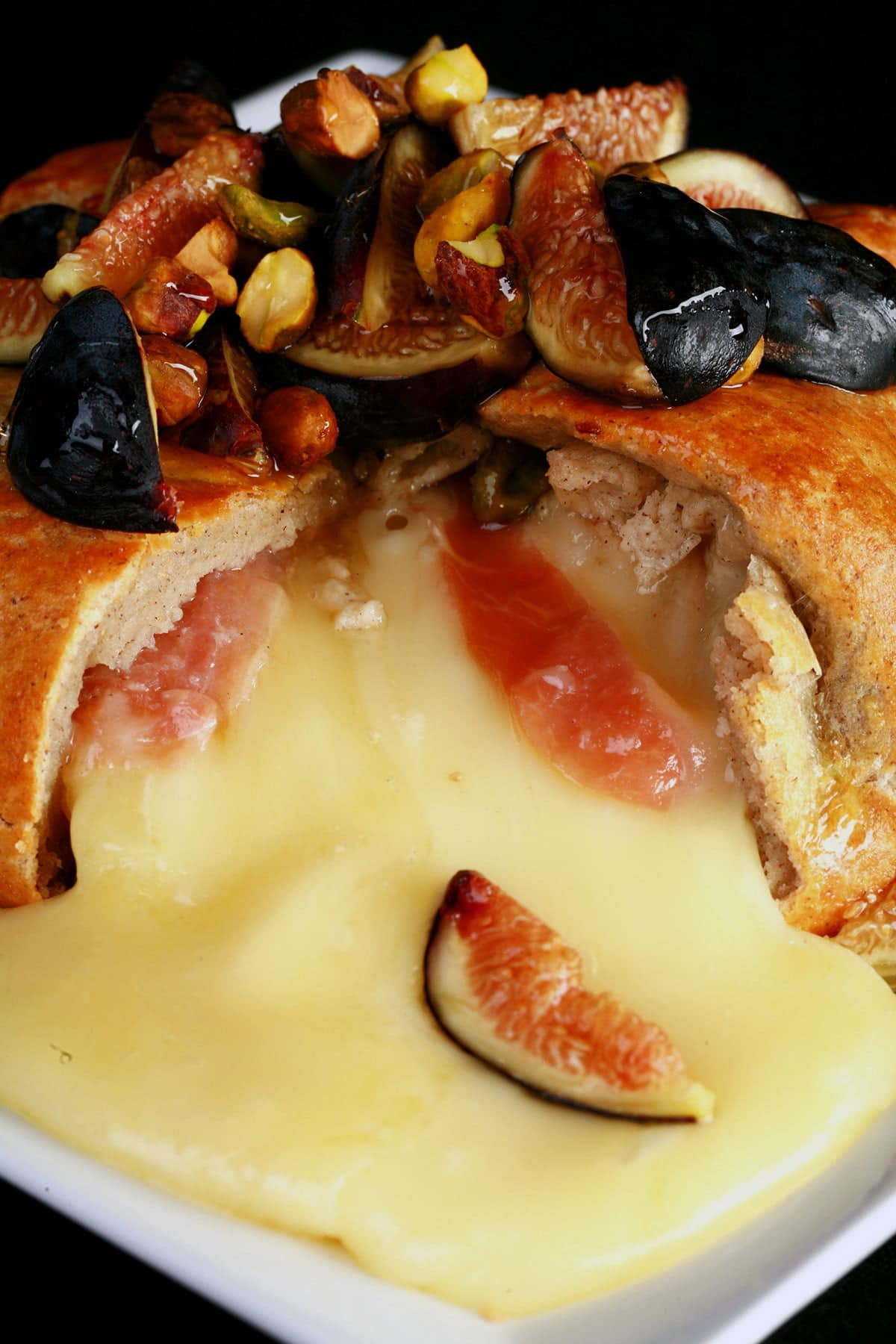 A brie en croute is broken open, with brie and bits of prosciutto pouring out. It's topped with figs, pistachios, and honey.