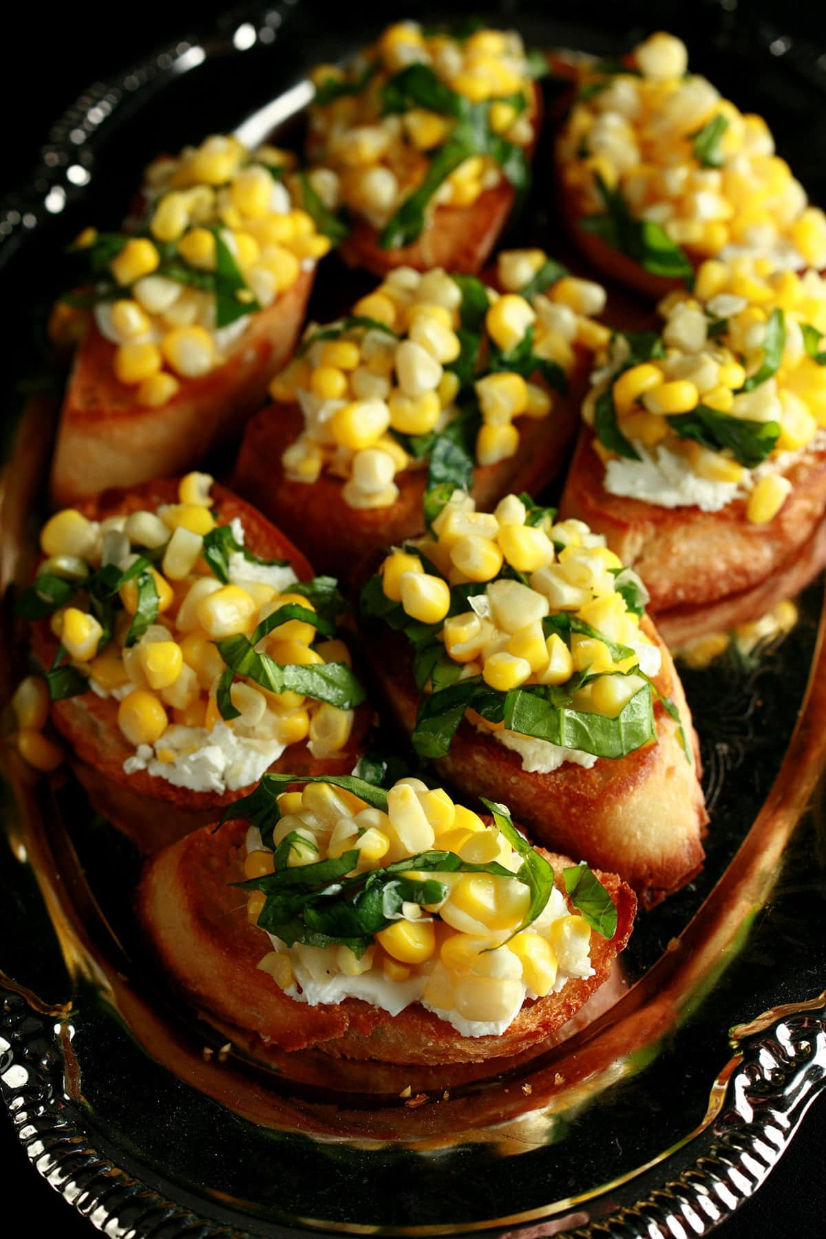A silver, oval shaped platter, filled with sweet corn bruschetta - slices of toasted baguette, smeared with goat cheese, and topped with sweet corn kernels, basil, and balsamic vinegar.