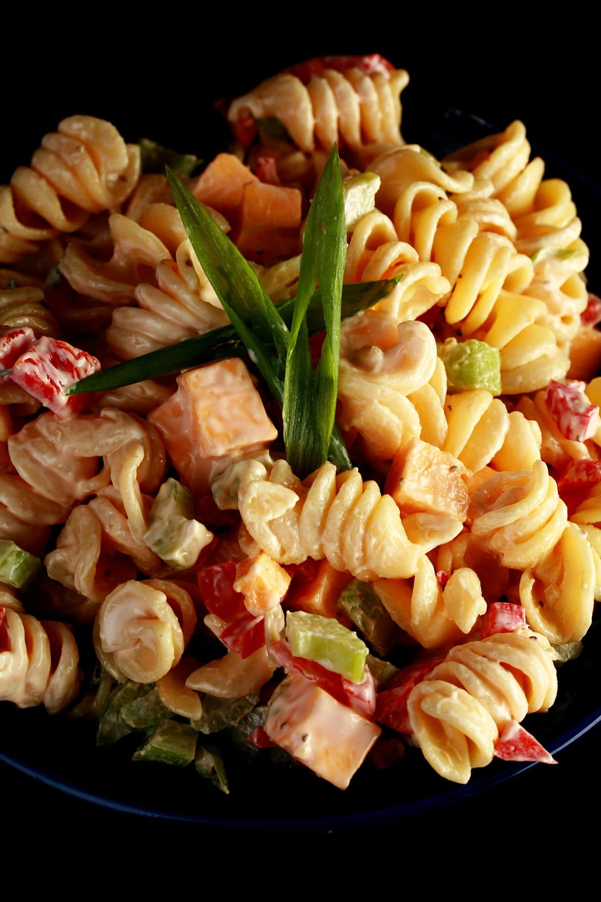 A blue bowl overflowing with a rotini based macaroni salad. Cubes of cheese, red peppers, celery slices, and green onion are all visible.