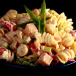A blue bowl overflowing with a rotini based pasta salad. Cubes of cheese, red peppers, celery slices, and green onion are all visible.
