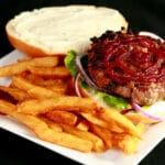 An open faced burger on a plate with fries. The burger has a large ruby red swirl of roasted beet ketchup on it.