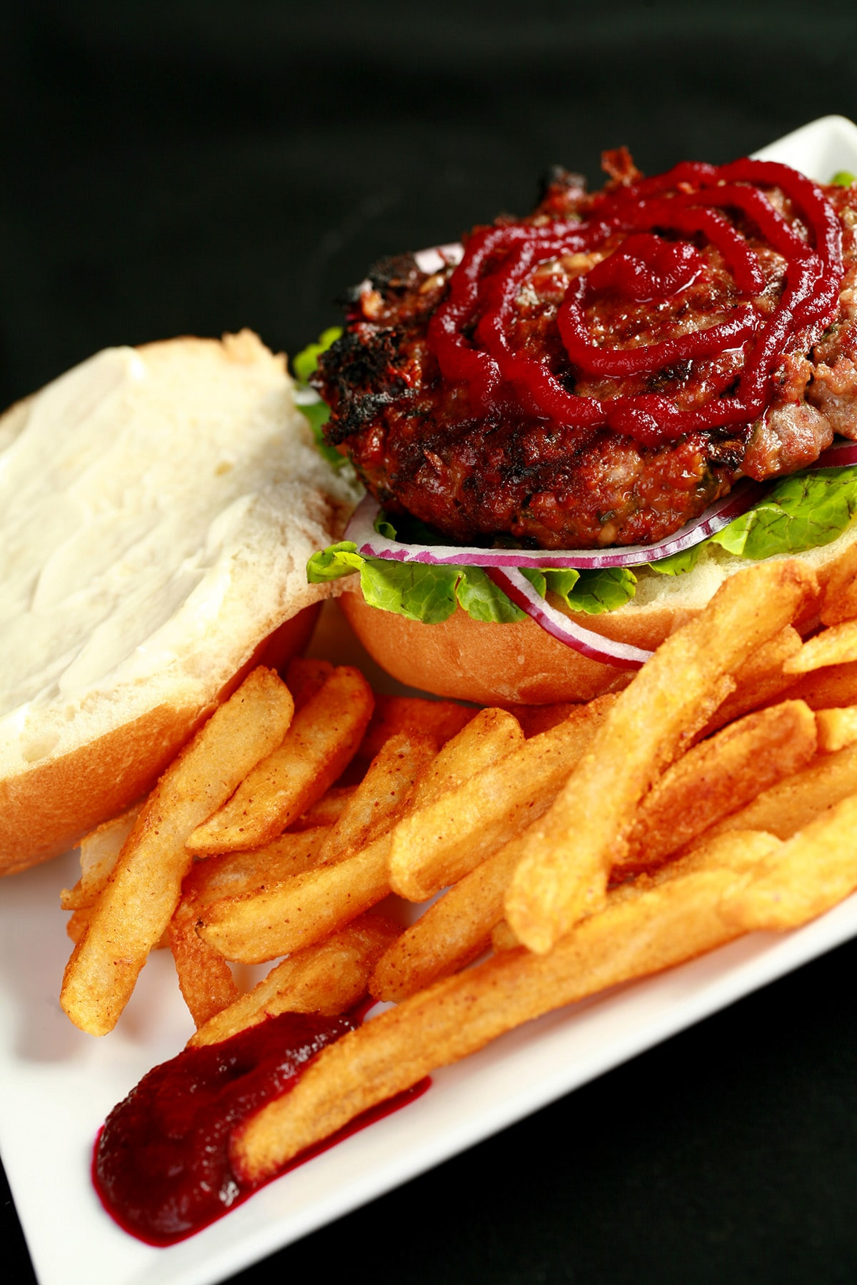 An open faced burger on a plate with fries. The burger has a large ruby red swirl of beet ketchup on it.
