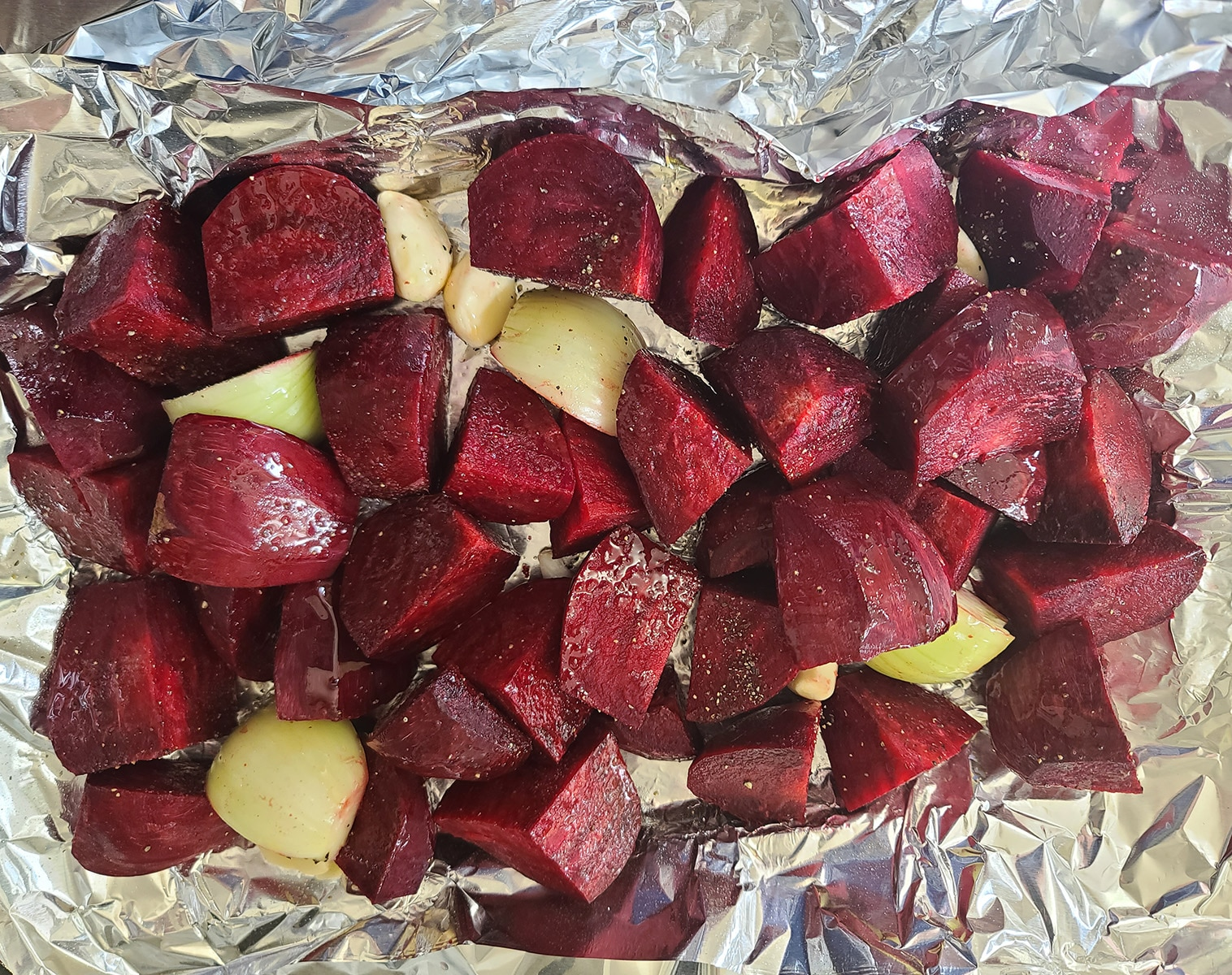 Chopped peeled beets, onions, and garlic cloves on foil.