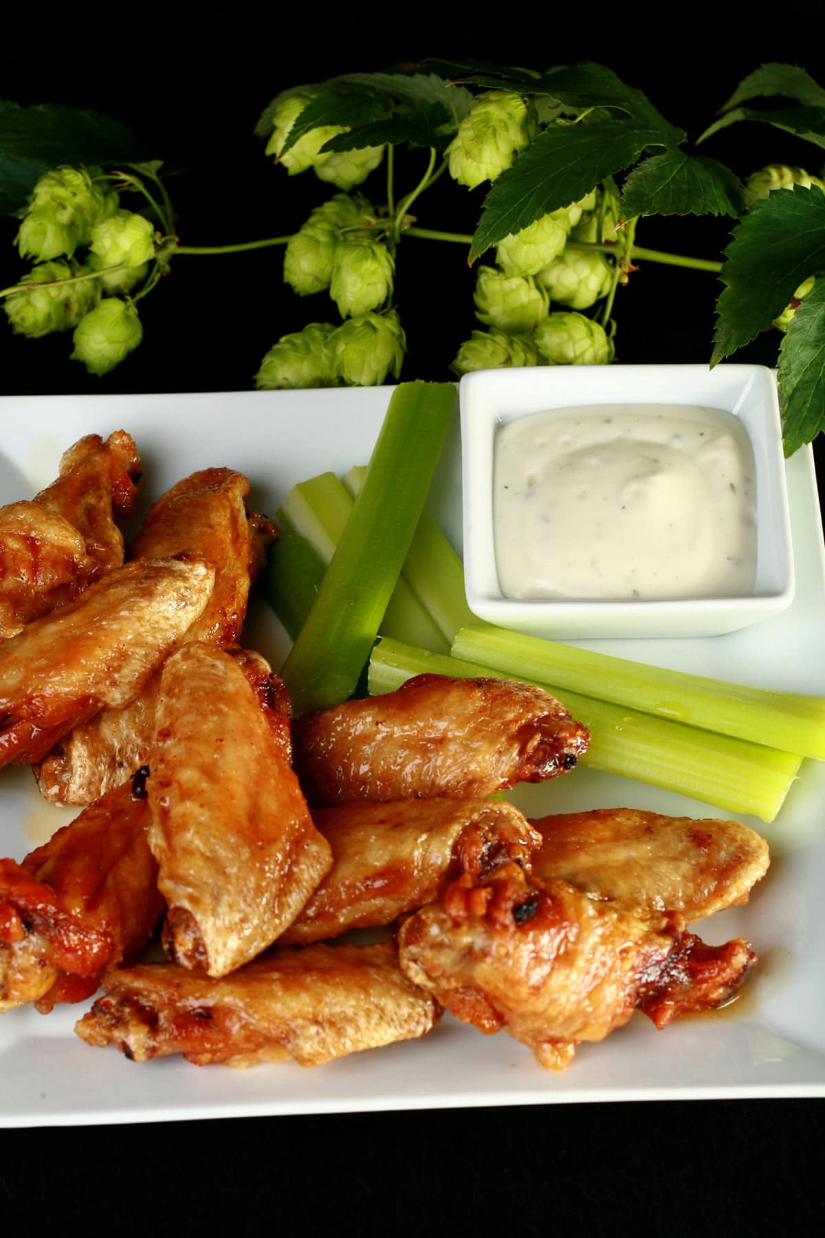 A plate of deep fried, Hoppy Citrus IPA Glazed Wings. They;re on a plate with celery sticks and a little bowl of ranch sauce, and the plate is surrounded by fresh hop bines.