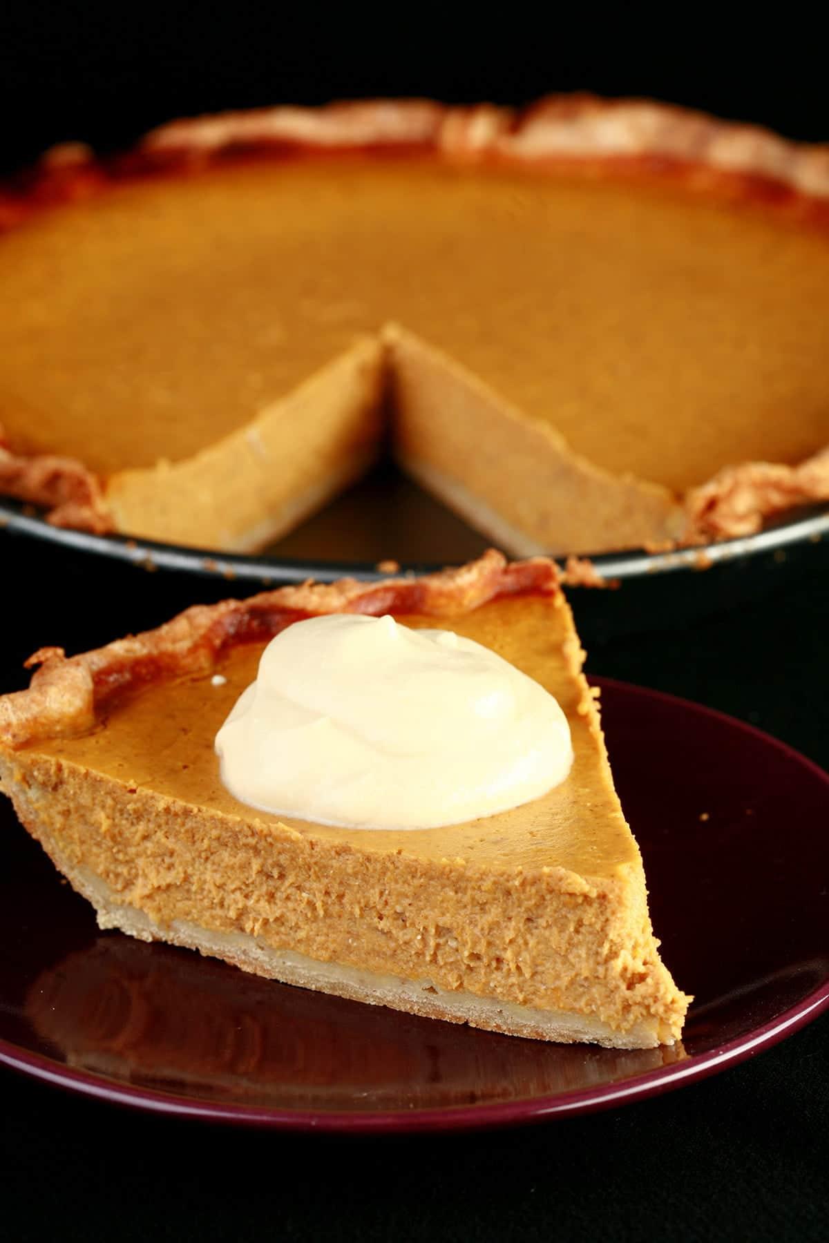 A slice of gluten-free maple pumpkin pie with maple cream, in front of a whole pumpkin pie.