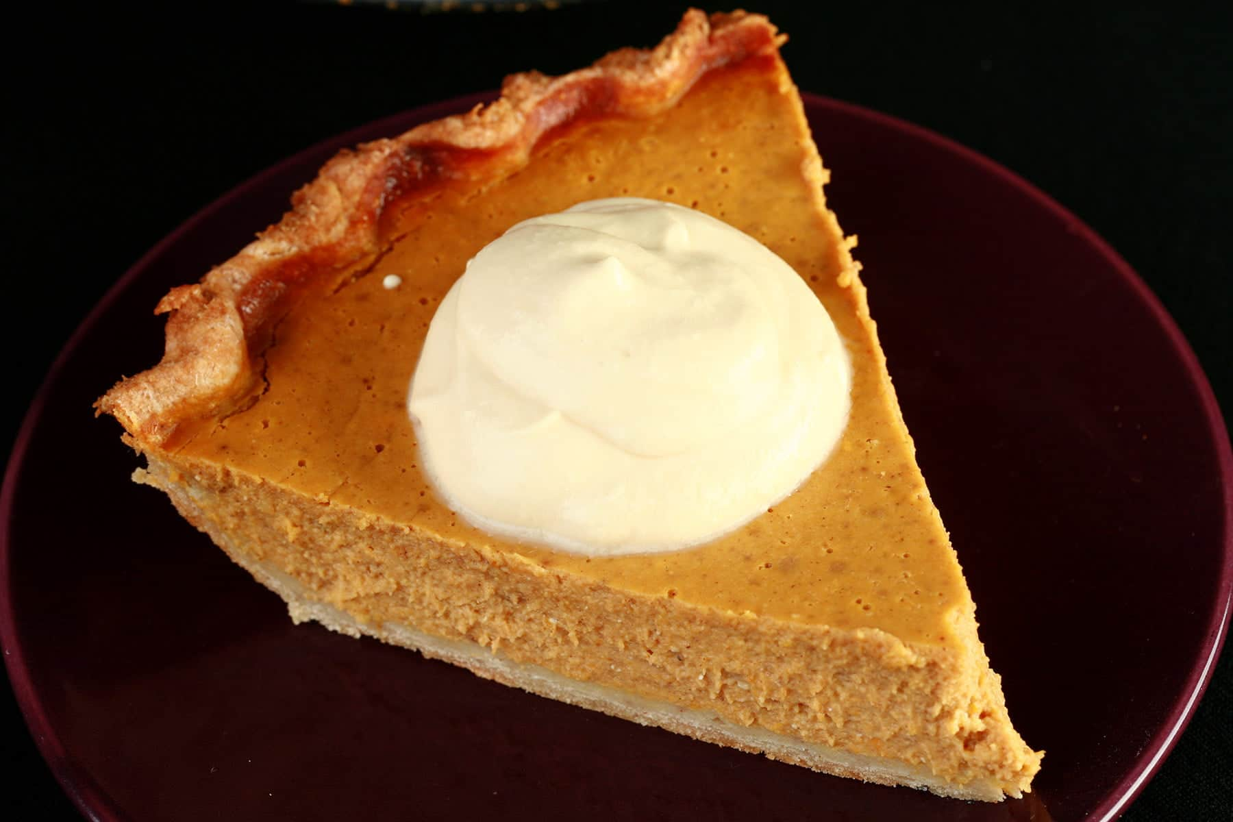 A slice of pumpkin pie with maple cream.