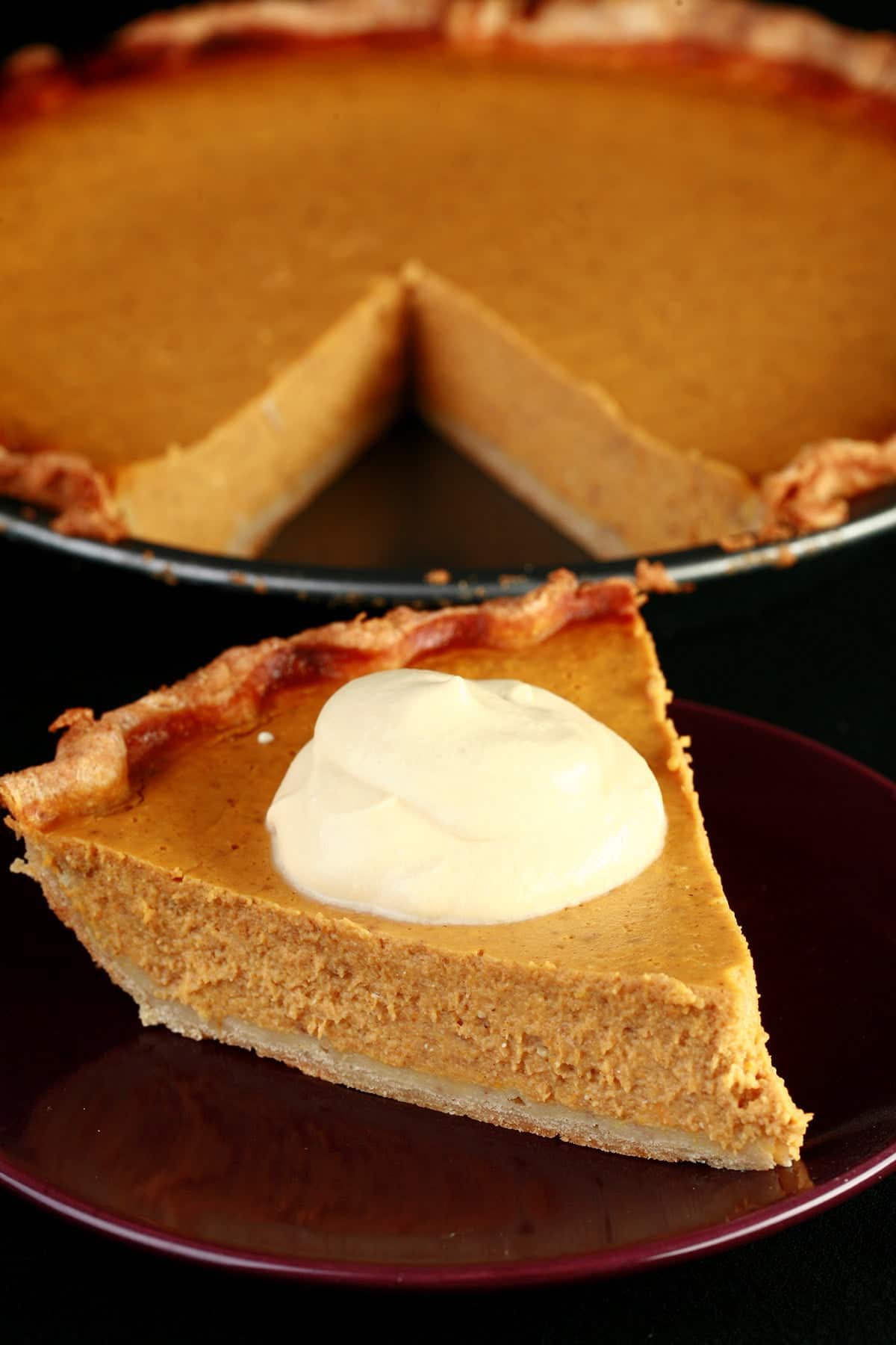 A slice of pumpkin pie with maple cream, in front of a whole pumpkin pie.