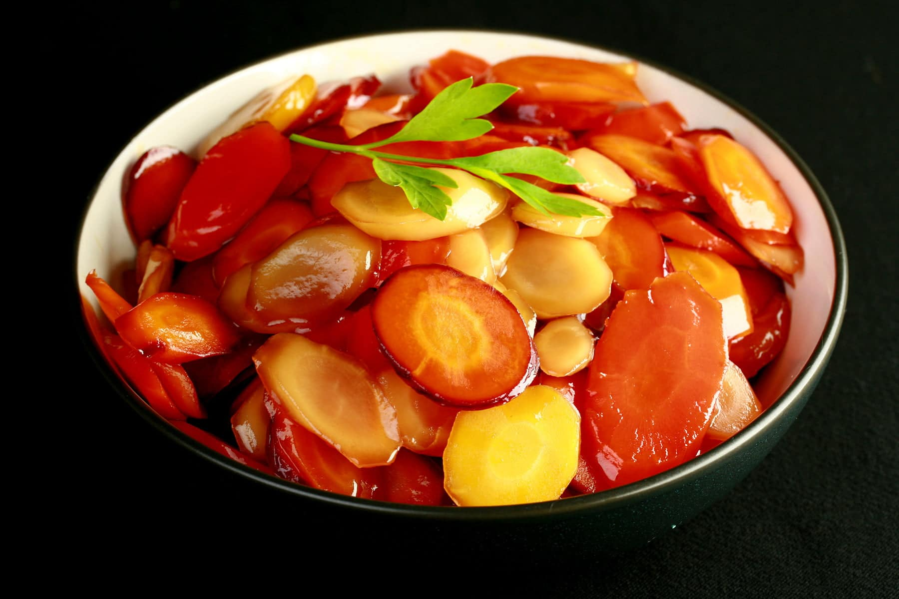 A bowl of brightly coloured carrot slices, in a shiny glaze. There is a small piece of flat leaf parsley on top, as garnish.