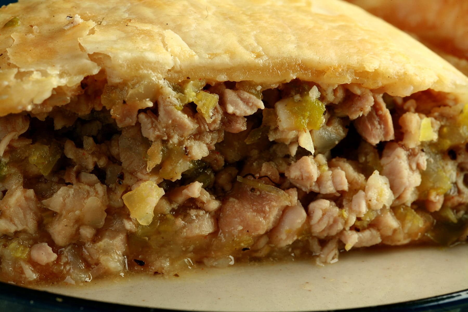 A slice of savory alligator pie, on a small white plate. The filling shows chunks of meat and vegetables, like celery.
