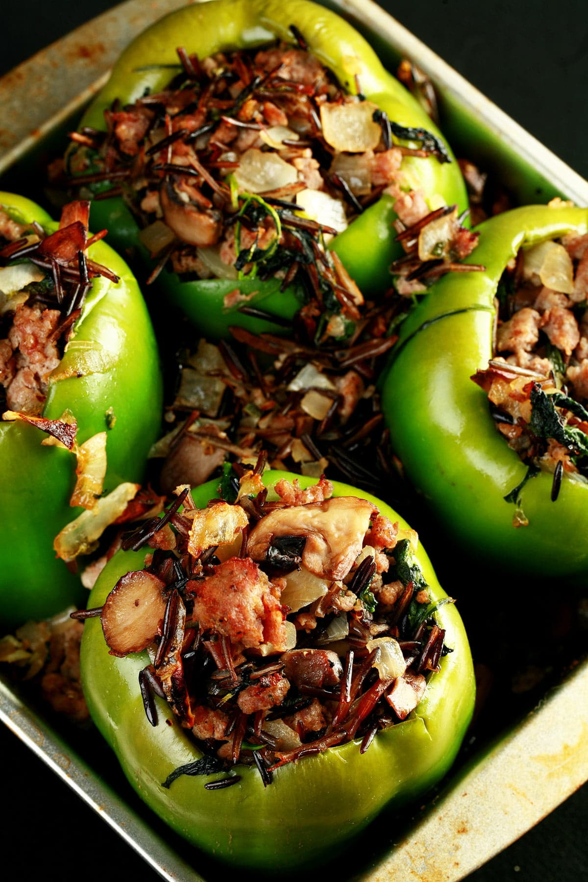Close up view of a pan of wild rice and sausage stuffed peppers.