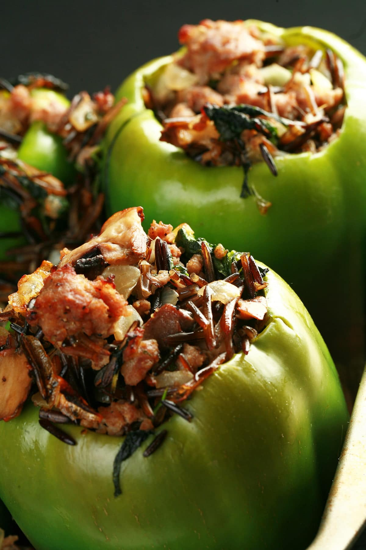 Close up photo of a pan of green peppers that have been hollowed out and stuffed with wild rice, mushrooms, and sausage.