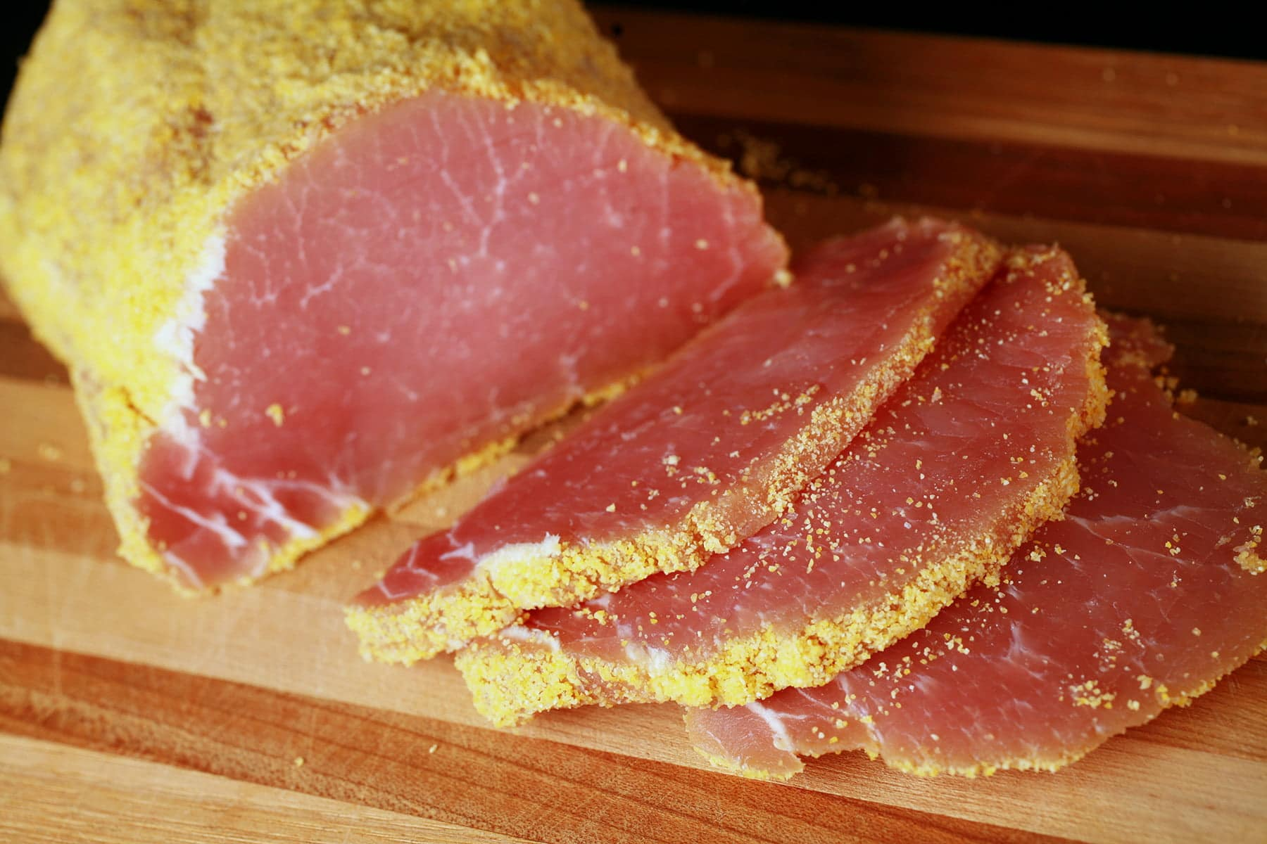 A cured loin of pork that has been rolled in cornmeal and sliced - proper pea meal bacon!