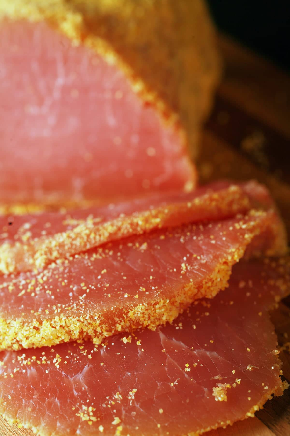 A cured loin of pork that has been rolled in cornmeal and sliced - proper bacon!