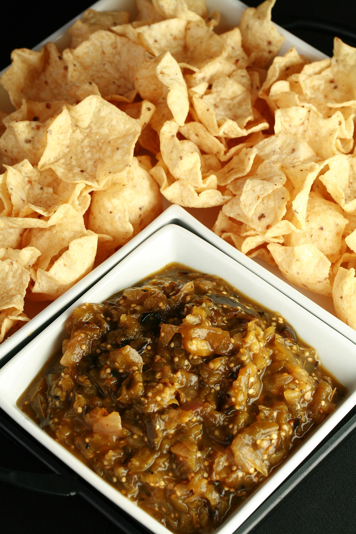 A large square bowl of roasted salsa verde, surrounded by white corn chips.