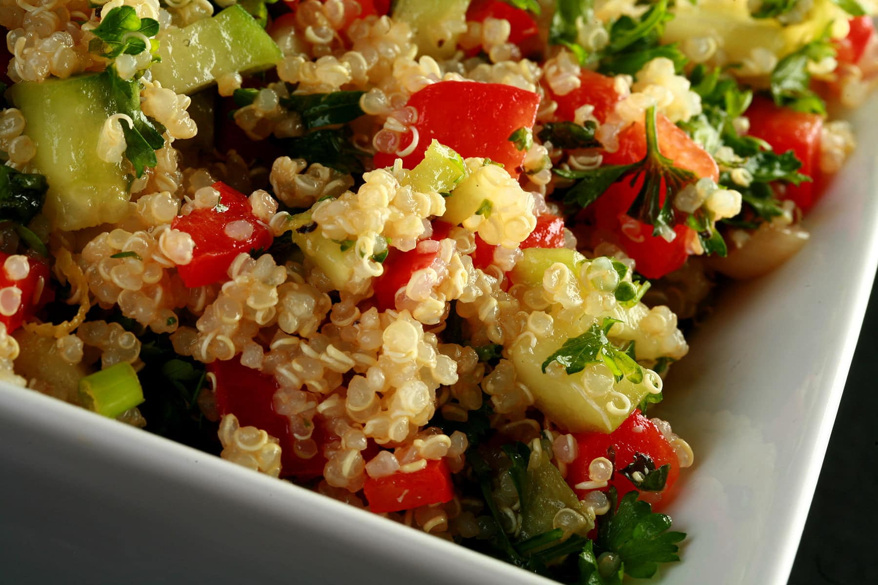 A square, white bowl holds a no-tomato quinoa based tabbouleh.  Beige quinoa, red pepper, cucumber, and parsley is visible throughout.