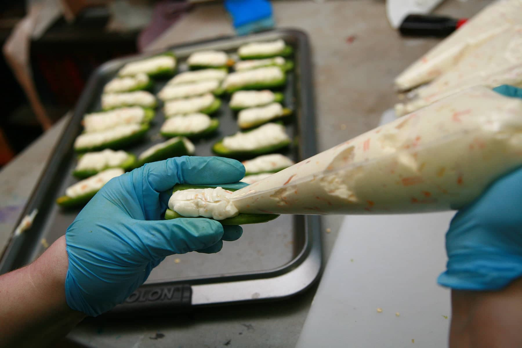 Gloved hands use a pastry bag to pipe cheese mixture into a halved jalapeno pepper.