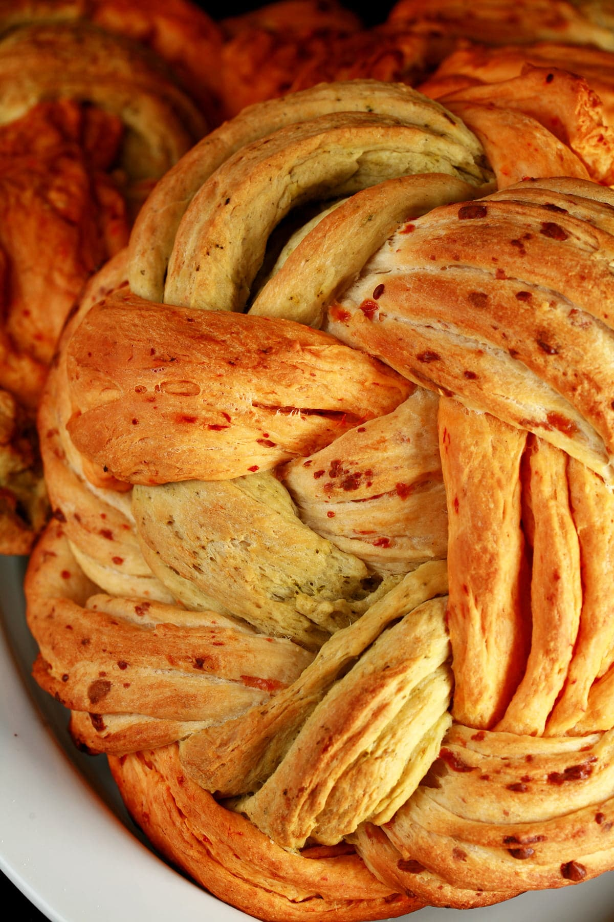 A large round loaf of a tri-colour braid bread. The breads are green/basil, tan/asiago, and red/roasted red pepper.