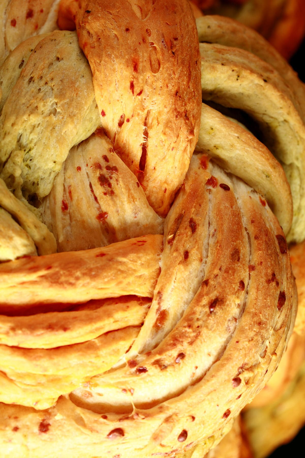 A large round loaf of a tri-colour bread braid. The breads are green/basil, tan/asiago, and red/roasted red pepper.
