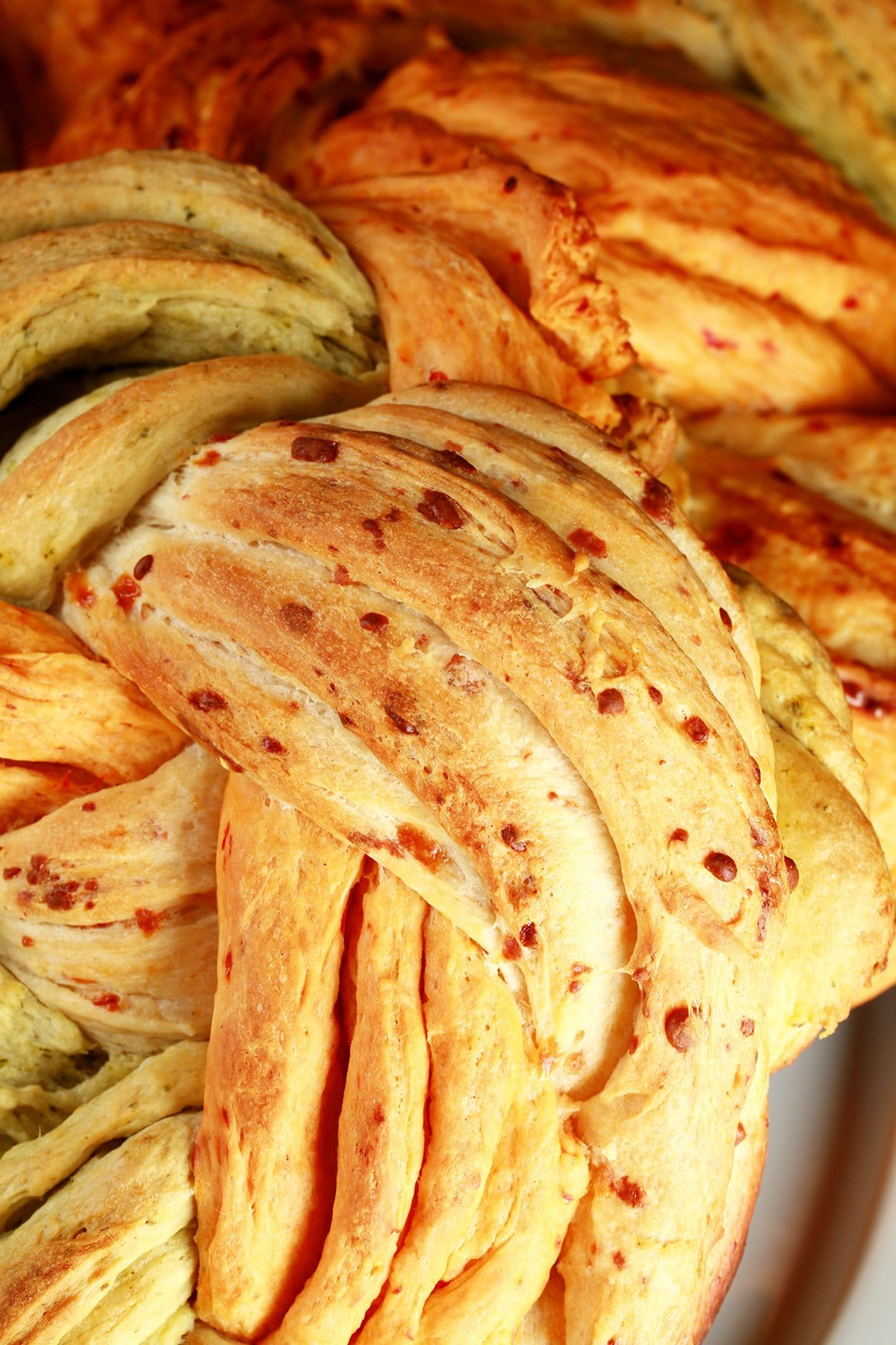 A close up view of a loaf of a tri-colour braid bread. The breads are green/basil, tan/asiago, and red/roasted red pepper.