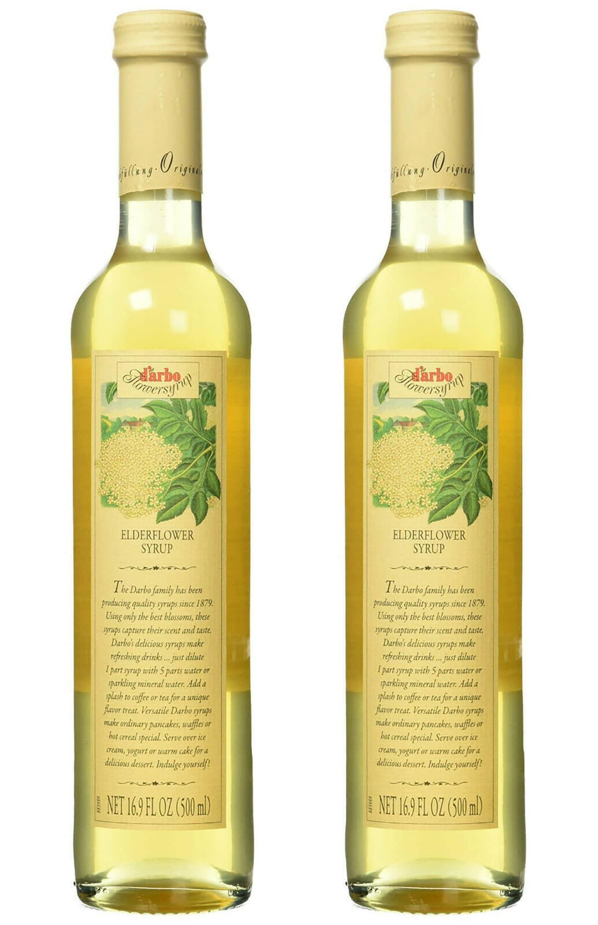 Two tall, slender bottles of elderflower syrup.