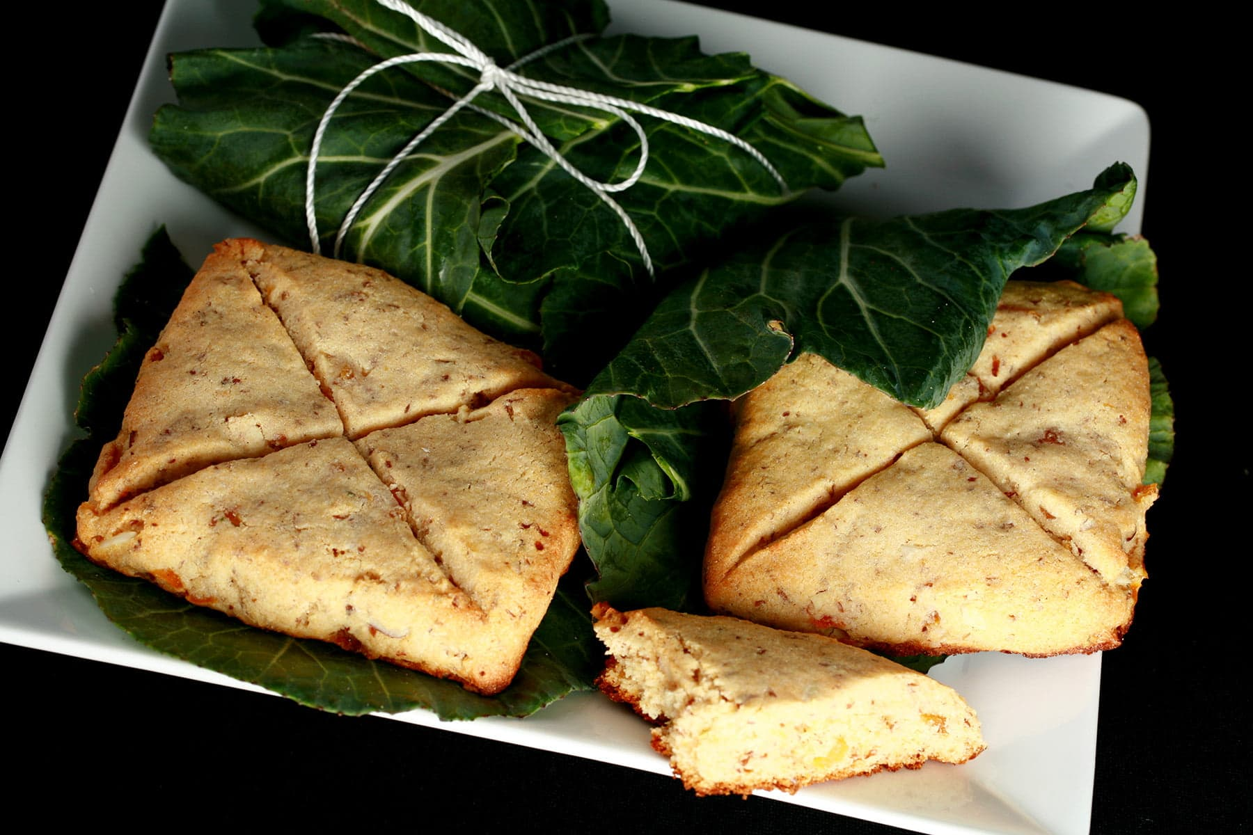 A square white plate displays 3 pieces of Lembas bread. Two of the square biscuits - each marked with an X cut - are unwrapped, while the 3 is still neatly packaged in a large leaf, and tied with twine.