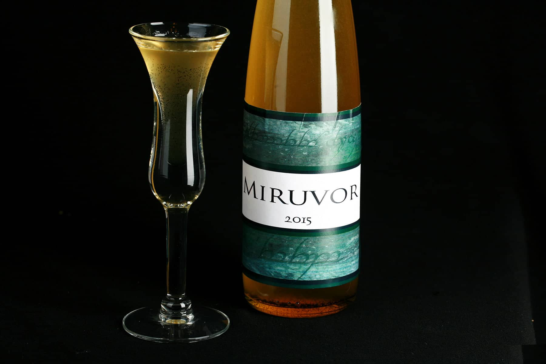 "A tall, slender wine bottle filled with a straw coloured liqueur is pictured next to a fluted shot glass filled with the same. The bottle is labelled ""Miruvor""."